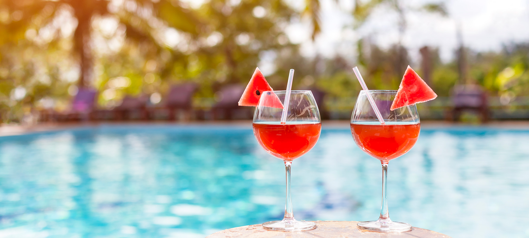 Two drinks sitting poolside
